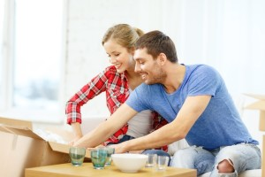 smiling couple unpacking kitchenwear